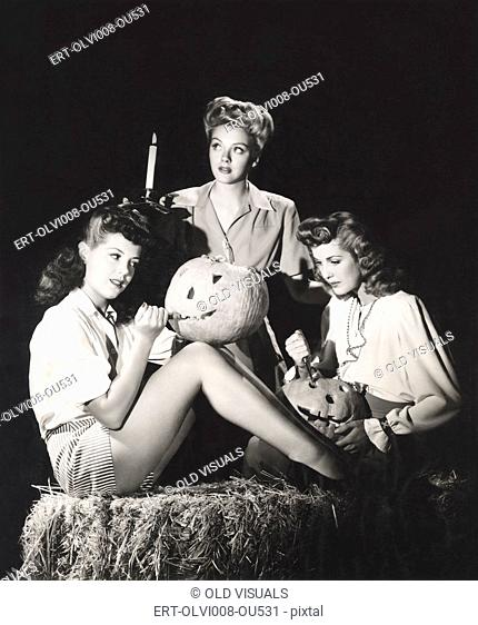 Three women in a barn carving pumpkins at night