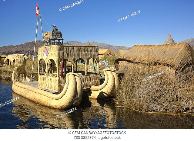 Tourist at the top of a Totora reed boat at the Uros Islands, Lake Titicaca, Puno Province, Peru, South America