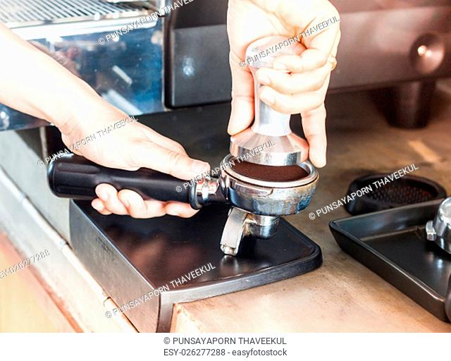 Barista with tamper for making espresso with vintage style, stock photo