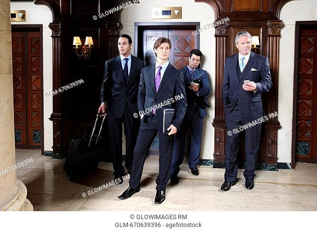 Four businessmen standing in a hotel lobby, Biltmore Hotel, Coral Gables, Florida, USA