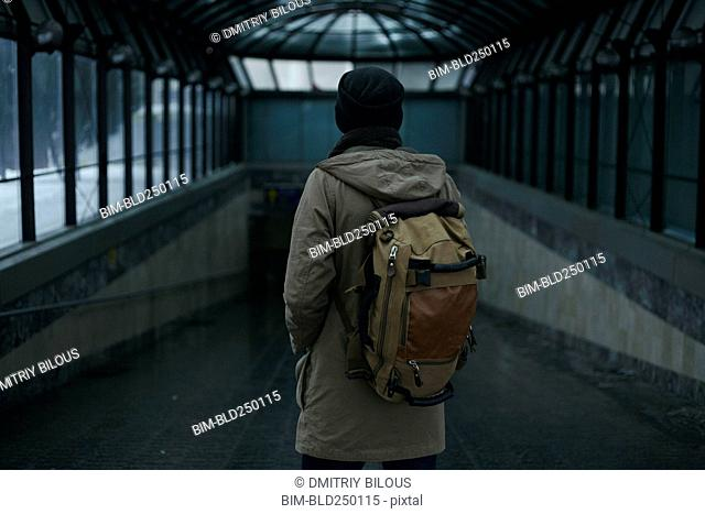 Man standing in tunnel carrying backpack