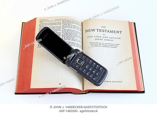 A cell phone laying on a Bible opened to the New Testament  Communication and religion in the modern age