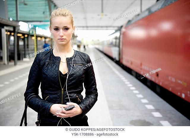 Young, blonde female, on the platform of a railway-station, waiting for her train