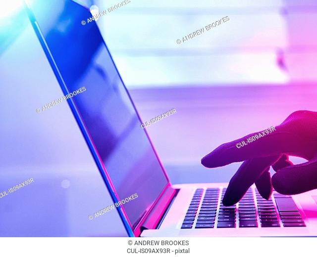 Gloved hand hacking laptop computer