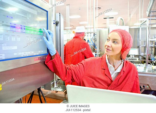 Worker using touch screen control panel on production line in food processing plant