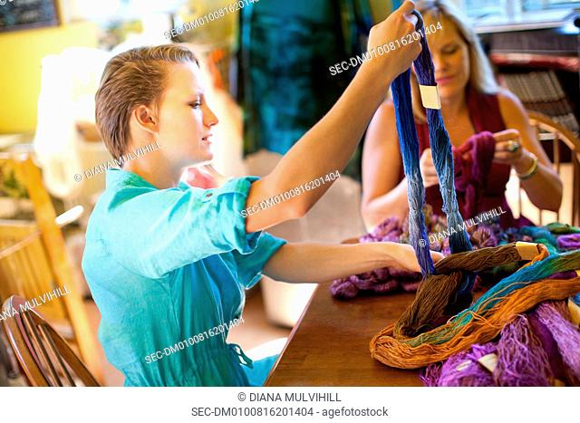 Mother and daughter preparing yarn for scarfs
