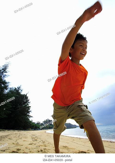 Low angle view of a boy walking on the beach