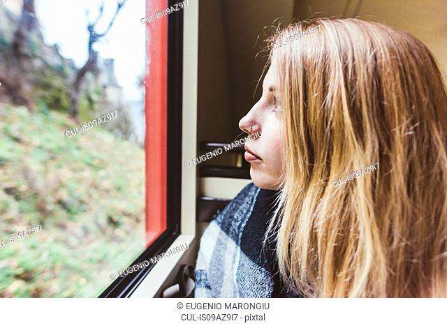Young woman staring through funicular window, Como, Italy