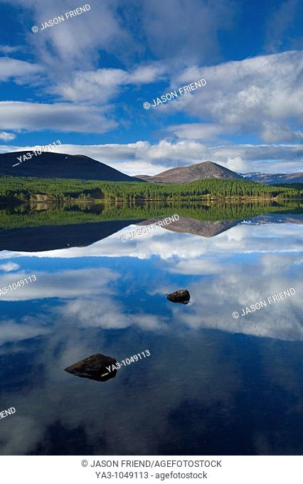 Scotland, Scottish Highlands, Cairngorms National Park  Clouds, forest and mountains reflected upon the still waters of Loch Morlich