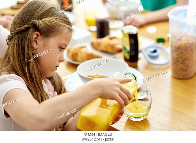 A family having breakfast. A girl pouring orange juice into a glass