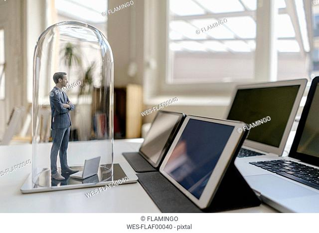 Businessman figurine standing under glass bell on desk, facing mobile devices