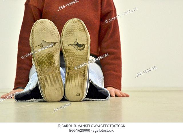 woman sitting on floor, wearing worn out sneakers
