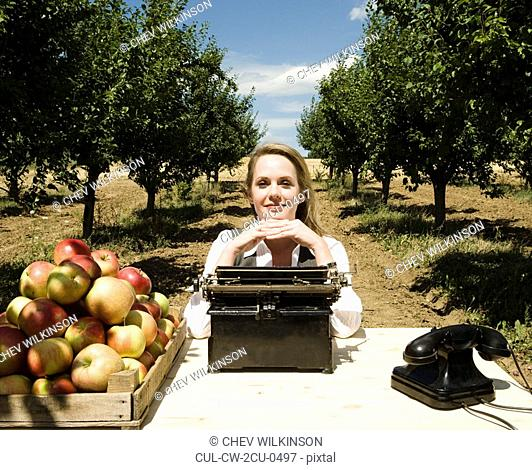 Woman sitting at desk in orchard