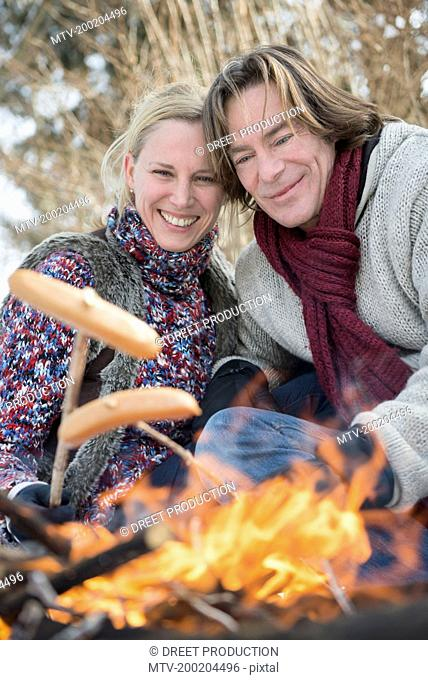 Couple barbecueing sausage on camp fire, Bavaria, Germany