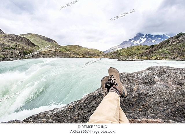 Sitting on a rock with a view of a rushing mountain river; Tores Del Paine, Magallanes, Chile