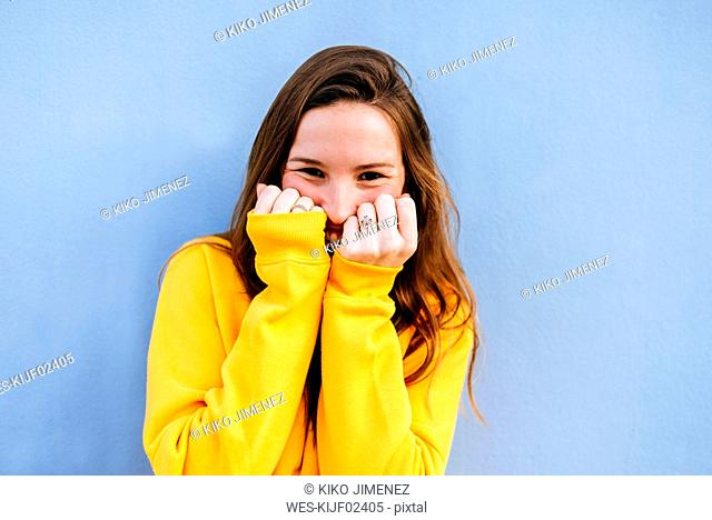 Portrait of happy young woman with yellow pullover at blue wall