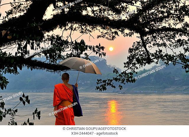 monk at sunset on Mekong River at Luang Prabang, Laos, Southeast Asia