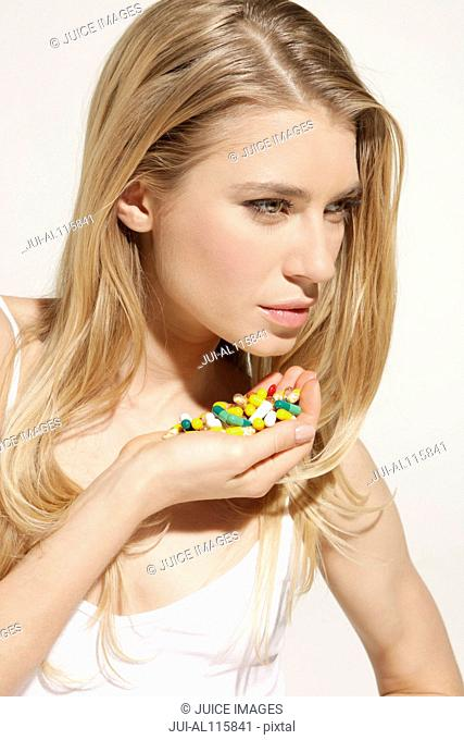 Young woman holding heap of pills in studio