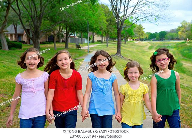 Children group of sisters girls and friends walking happy in the park outdoor