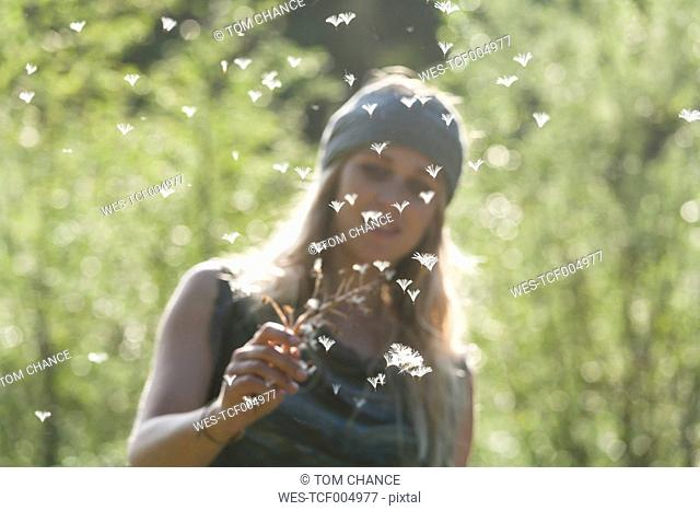 Woman watching flying seeds of an umbel