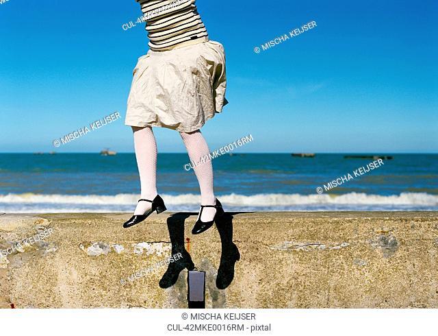 Girl jumping on stone wall at beach