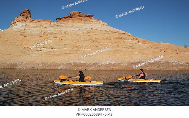 two people paddling kayaks