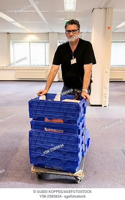 Tilburg, Netherlands. Middle aged technical worker pushing carts with computer electronics during the clean up of an abandoned office building