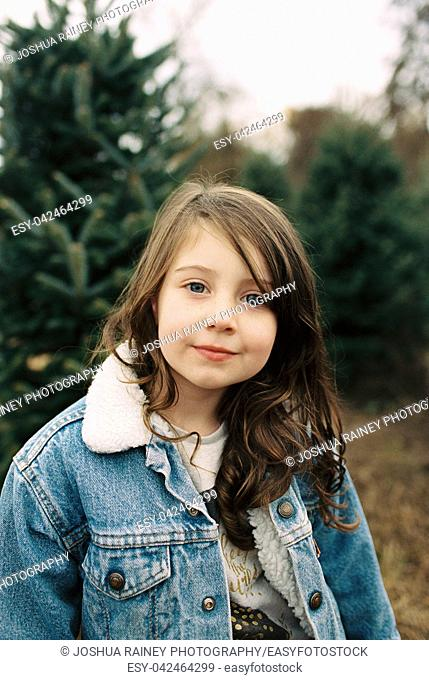 Five year old girl dressed for a fun outing in a winter or fall lifestyle portrait featuring the young kid in an image from a film scan