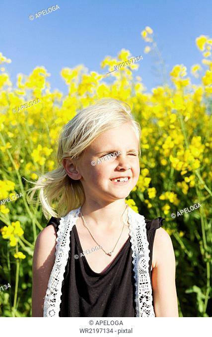 Girl winking eyes while standing at rapeseed field on sunny day
