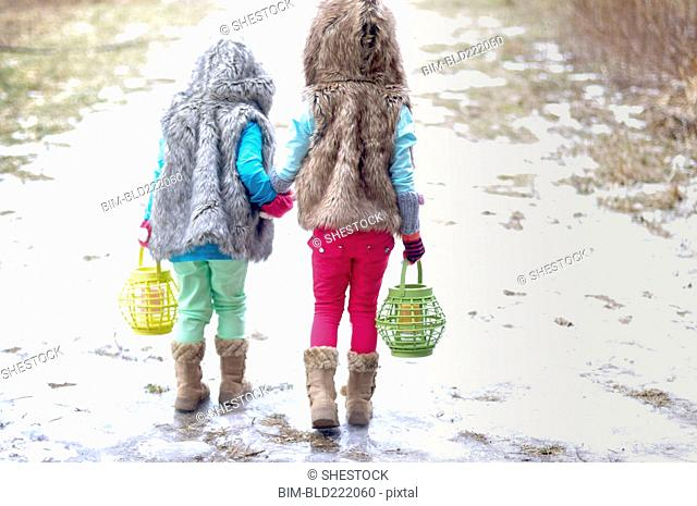 Caucasian girls holding hands in snow