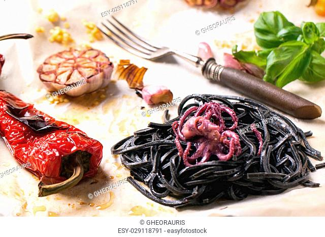 Black spaghetti served on crumpled baking paper with octopus, grilled paprika, garlic and fresh basil. See series