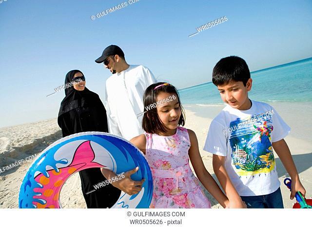 Family walking on beach, smiling
