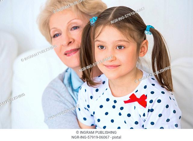 Lovely little girl with her grandmother having fun and happy moments together at home