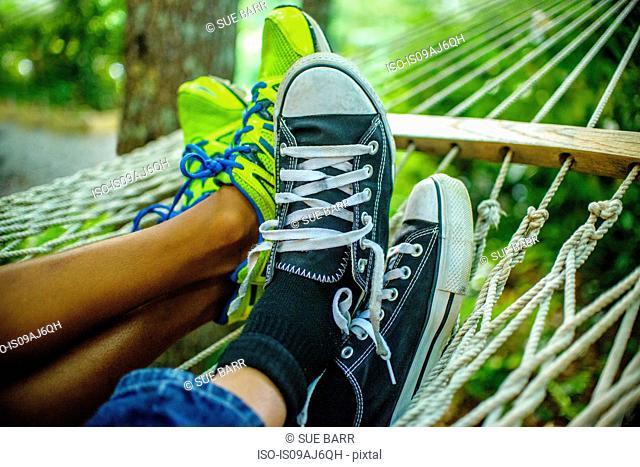 Legs of teenage boys lying in hammock