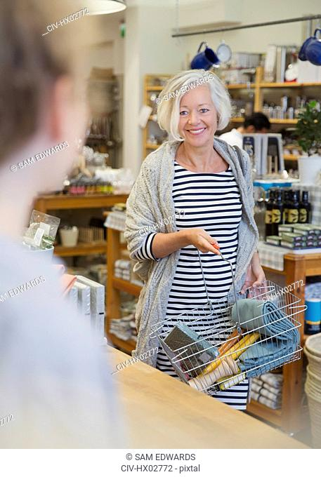Smiling mature woman shopping, nearing checkout counter in shop