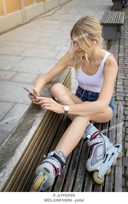 Smiling young inline-skater sitting on bench listening music with earphones and cell phone