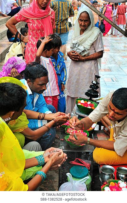 Priest blessing pilgrims at Har Ki Pairi ghat by the Ganges River