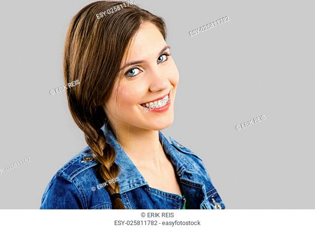 Portrait of a beautiful woman smiling over a grey background