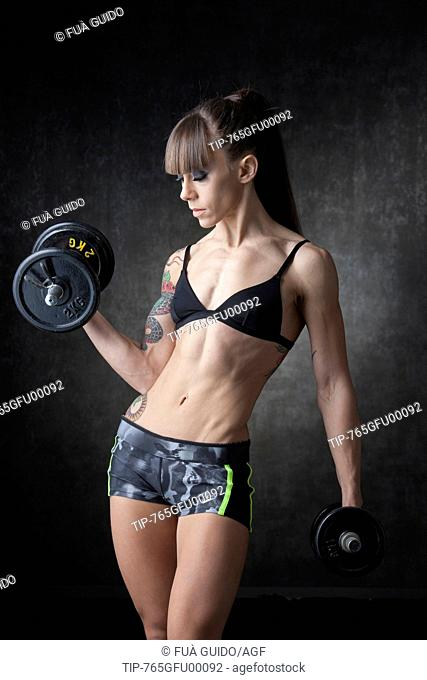 Young sporty woman lifting weights