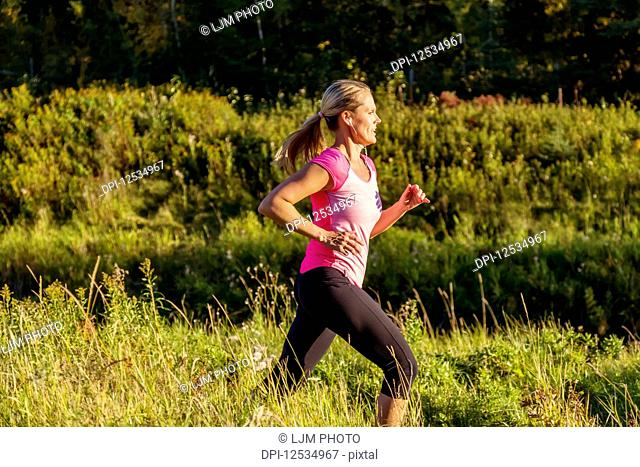 An attractive middle-aged woman wearing active wear and listening to music runs along a creek in a city park at sunset on a warm autumn evening; Edmonton