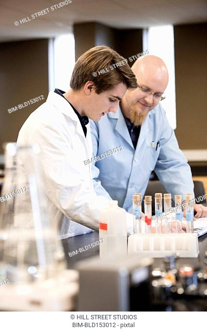 Caucasian teacher helping student in science lab