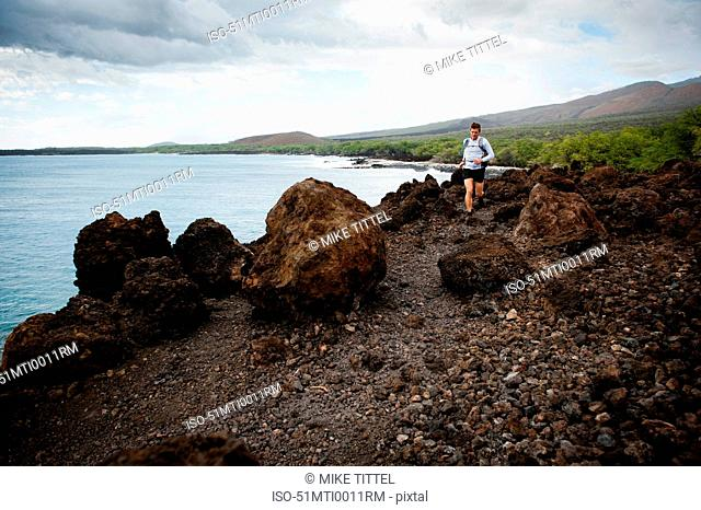 Man running on rocky rural trail