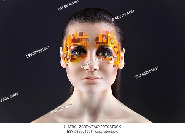 Portrait of a girl with an original make-up. Beauty close-up with orange and red rhinestones on a face of the model