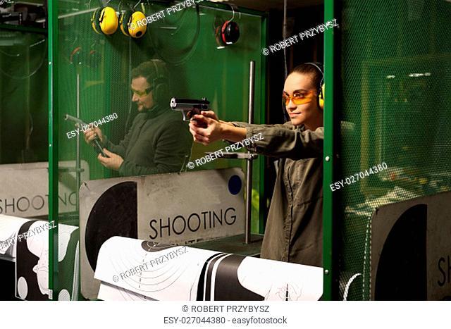 Glock, Kobieta strzela na strzelnicy. Kobieta bierze lekcje strzelania z broni krótkiej na strzelnicy sportowej