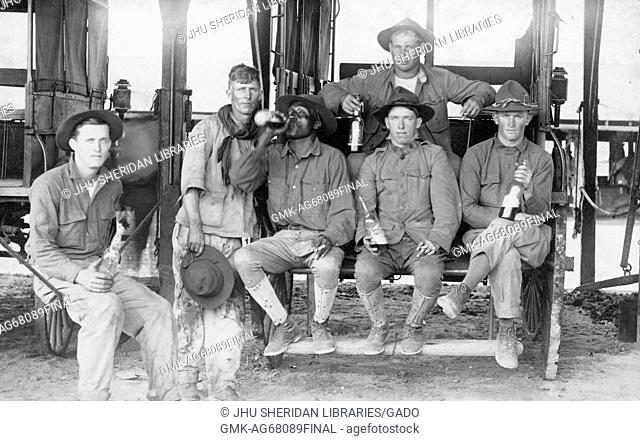 A group of workers, including one African-American man, with neutral expressions is gathered in front of and upon a wagon, drinking alcohol from glass bottles