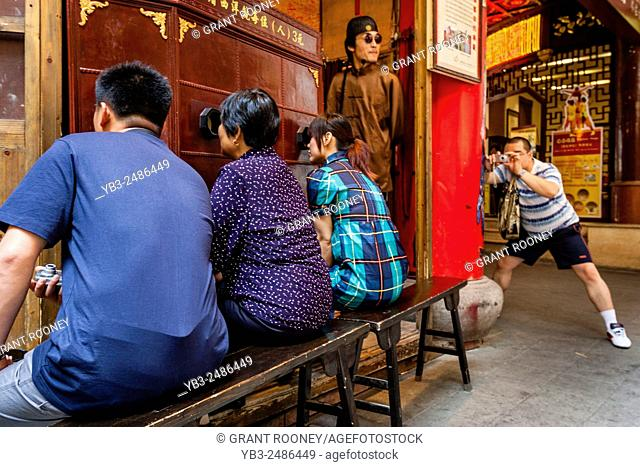A Man Takes A Photograph Of People Watching A Traditional Chinese Peep Show, Old Shanghai, Shanghai, China