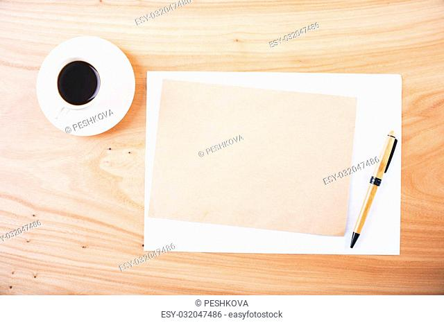 Top view of wooden desktop with blank brown and white paper sheets, coffee cup and pen. Mock up
