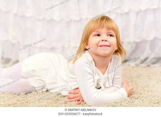 Happy pretty little girl lies on a carpet in the room
