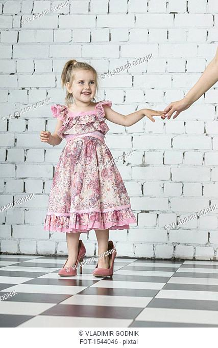 Happy girl in pink dress wearing oversized high heels standing at home