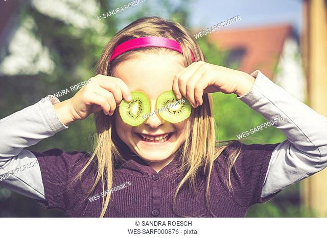 Laughing girl covering eyes with slices of kiwi